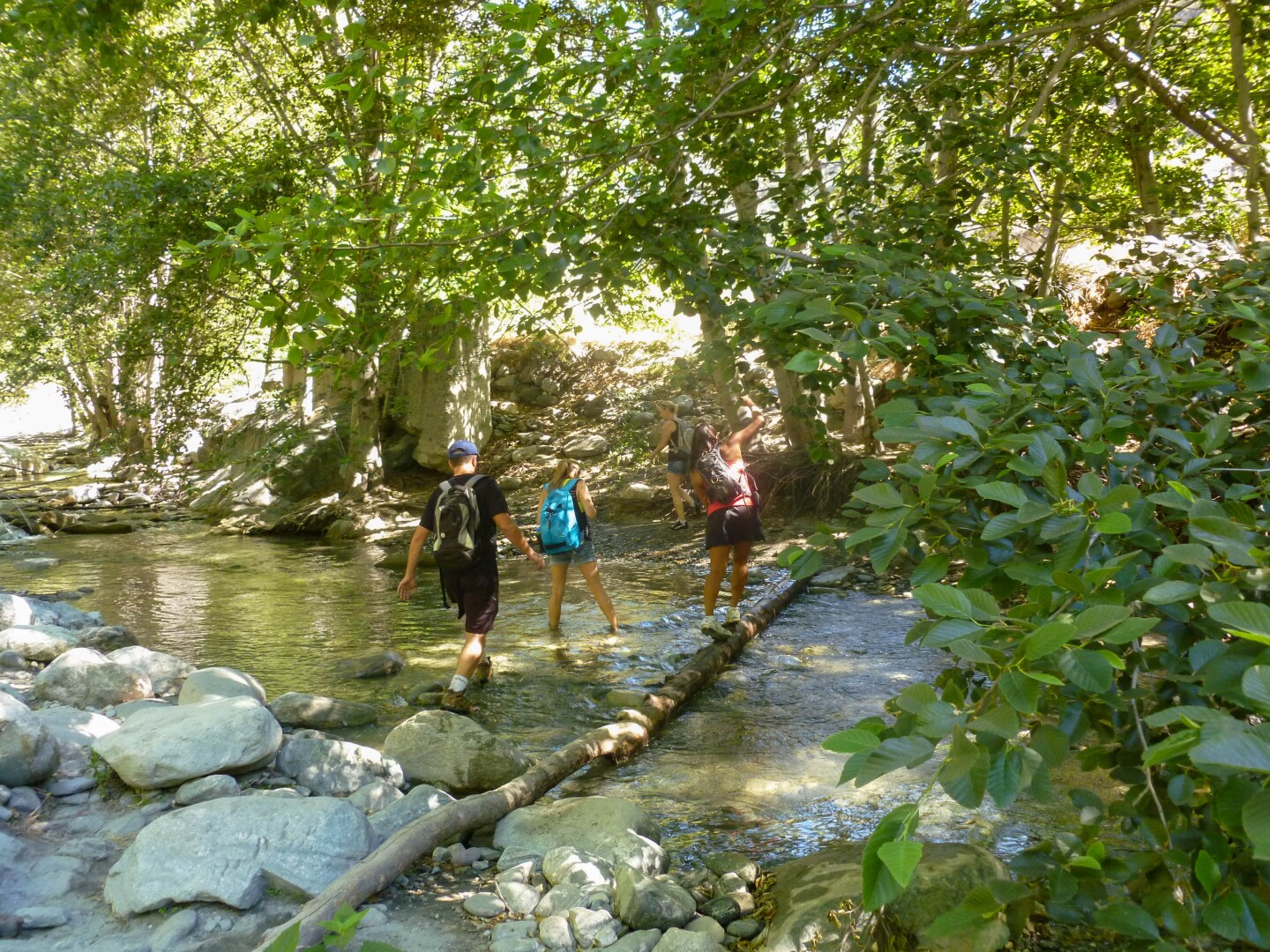Hikers wade through the East Fork of the San Gabriel River.