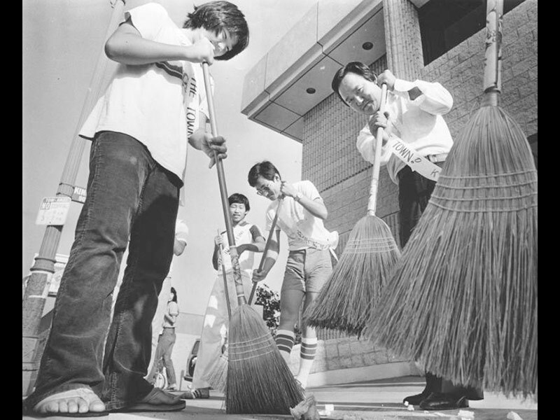 Black and white photo of Korean Americans sweeping the street