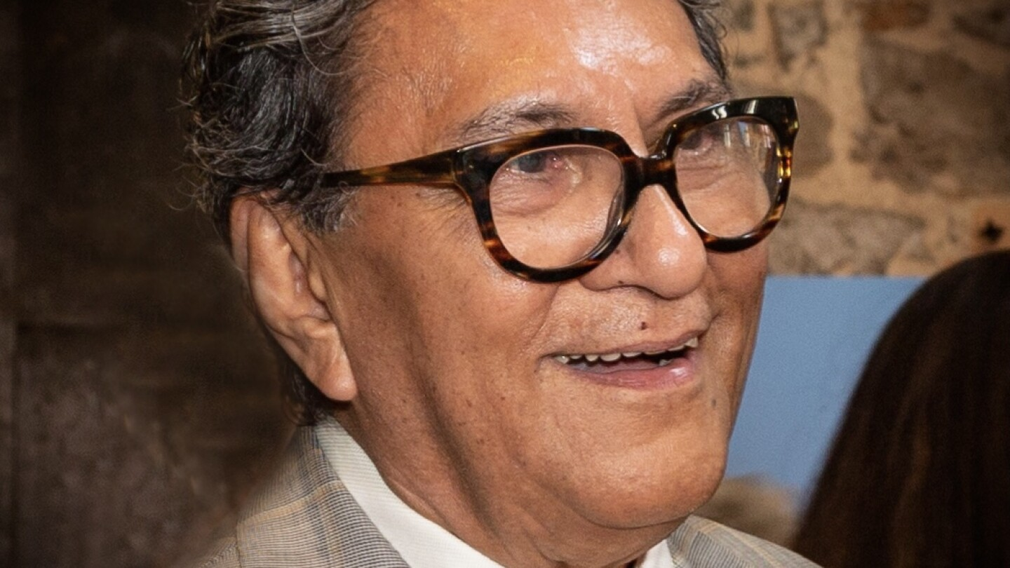 A portrait of Larry Baza from shoulders up. He's wearing thick, tortoise shell glasses, a beige plaid suit with yellow details and a gold tie. Baza is smiling and looking off to the side.