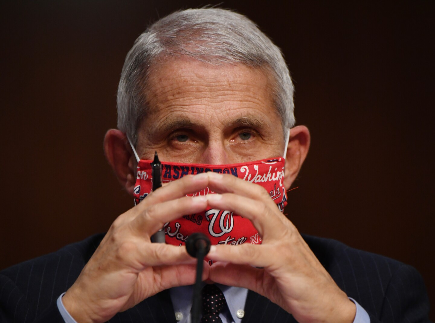 """Dr. Anthony Fauci, director of the National Institute for Allergy and Infectious Diseases, prepares to testify at a hearing of the Senate Health, Education, Labor and Pensions Committee on June 30, 2020 in Washington, DC. He is wearing a red face mask with the word """"Washington"""" on it."""