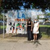 Two women stand in front of a mural by L.A. Versus Hate encouraging people to report hate incidents.