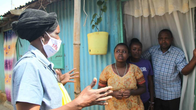 Community health volunteer Everlyne Akinyi Omondi talks to residents about the dangers of COVID-19 in Kawangware informal settlement in Nairobi, Kenya on May 27, 2020. | THOMSON REUTERS FOUNDATION/Nita Bhalla
