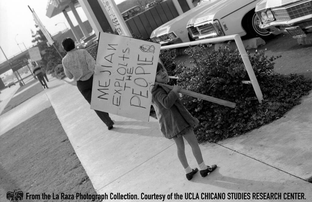 CSRC_LaRaza_B13F5S1_N019 Child holds protest sign on the street corner outside Mejian Chevrolet | La Raza photograph collection. Courtesy of UCLA Chicano Studies Research Center