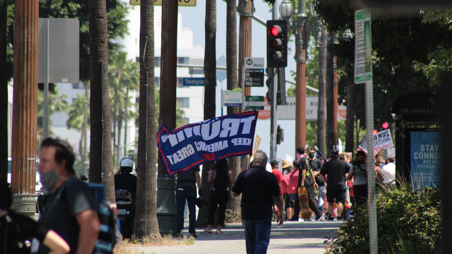 """Man with """"Trump 2020"""" flag walks down street, towards other protestors on May 1 in Downtown L.A. 