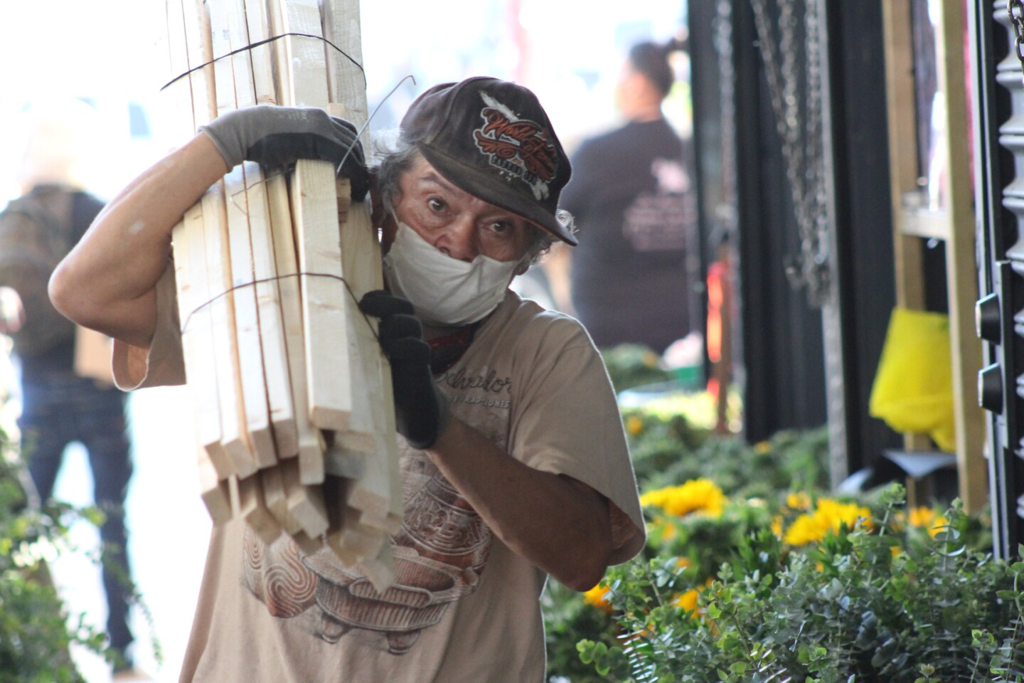 Man carries wood over his shoulder at Flower Market, as it reopened on May 8, 2020 | Karen Foshay
