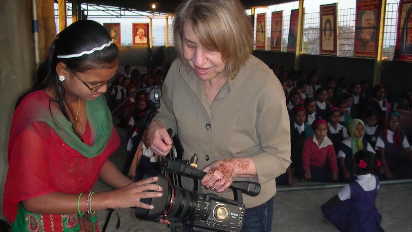A young girl examines a camera.