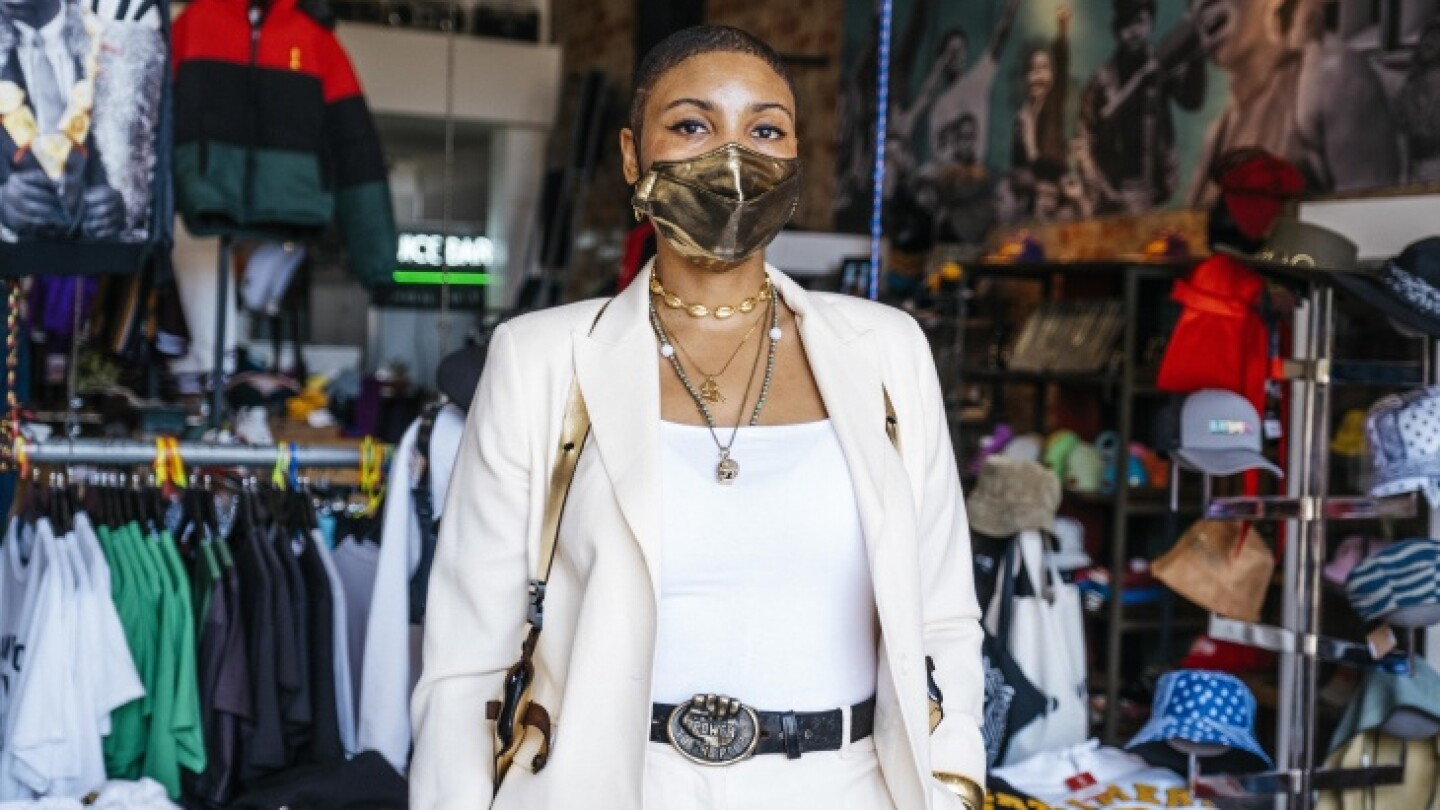 A woman in a shiny face mask and white suit in front of a clothing store