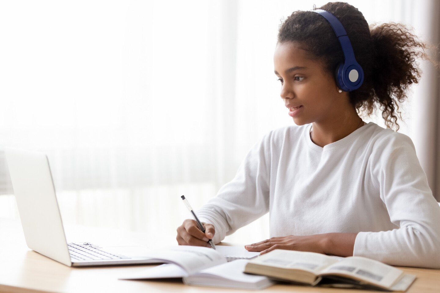 A young student wearing headphones and studying on a laptop.