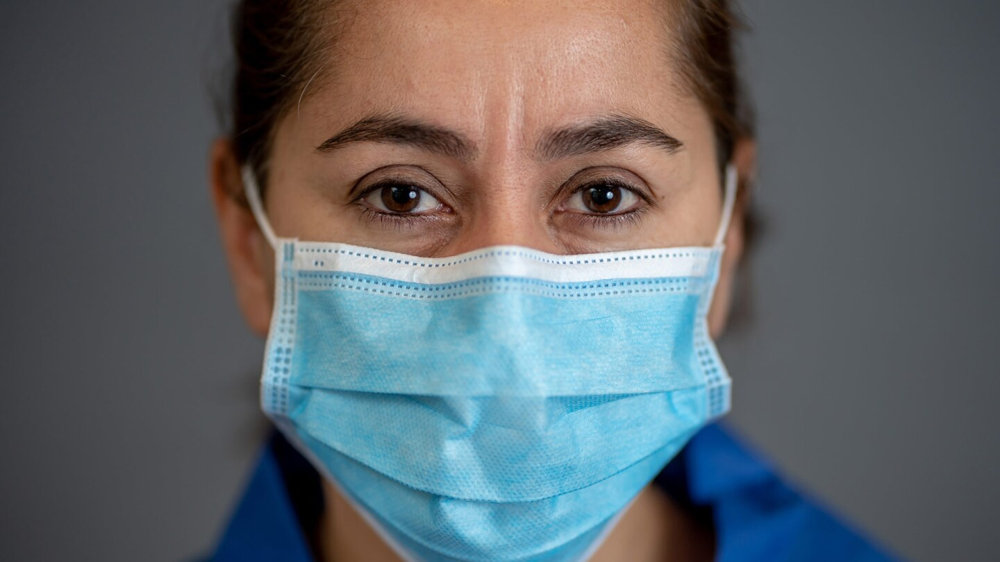 A Latina wears a mask. | iStock via Getty Images