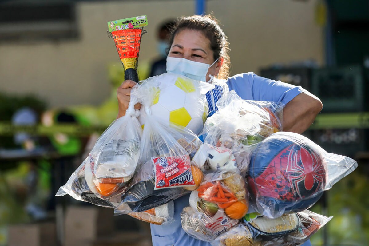 Beatrice Lopez walks out with sports items and meal bags distributed by LA84 Foundation and LAUSD at Grab and Go center at Thomas Alva Edison School.