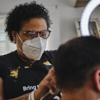 Carmelle concentrates while cutting a client's hair in her living room. | Chava Sanchez/LAist