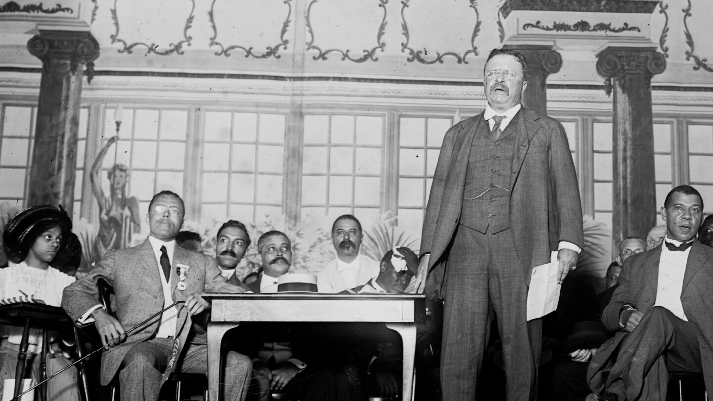 "Theodore Roosevelt (foreground) stands on stage before an audience with Booker T. Washington (right) sitting behind him. | Still from ""City Rising: The Informal Economy"""