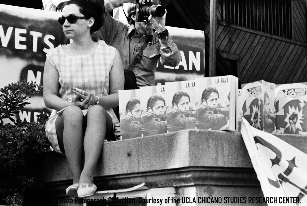 CSRC_LaRaza_B5F3C6_RR_012 Woman holds La Raza magazine copies at Fresno Moratorium | Raul Ruiz, La Raza photograph collection. Courtesy of UCLA Chicano Studies Research Center
