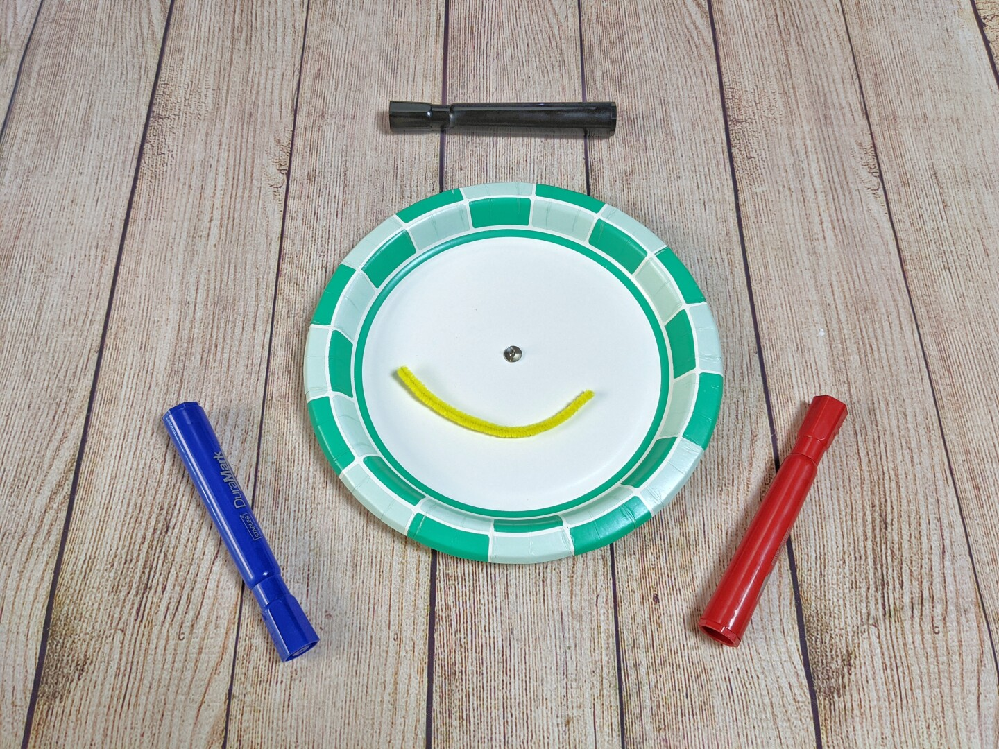 All you need for the spinner is a paper plate, a round head fastener, a pipe cleaner and a marker.