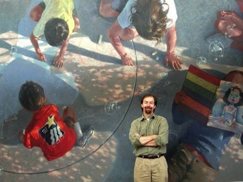 Kevin Stewart-Magee in front of one of his murals.