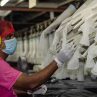 A worker makes checks at the Miditech Gloves' rubber glove factory in Malaysia in 2020.   Miditech Gloves via Thomson Reuters Foundation