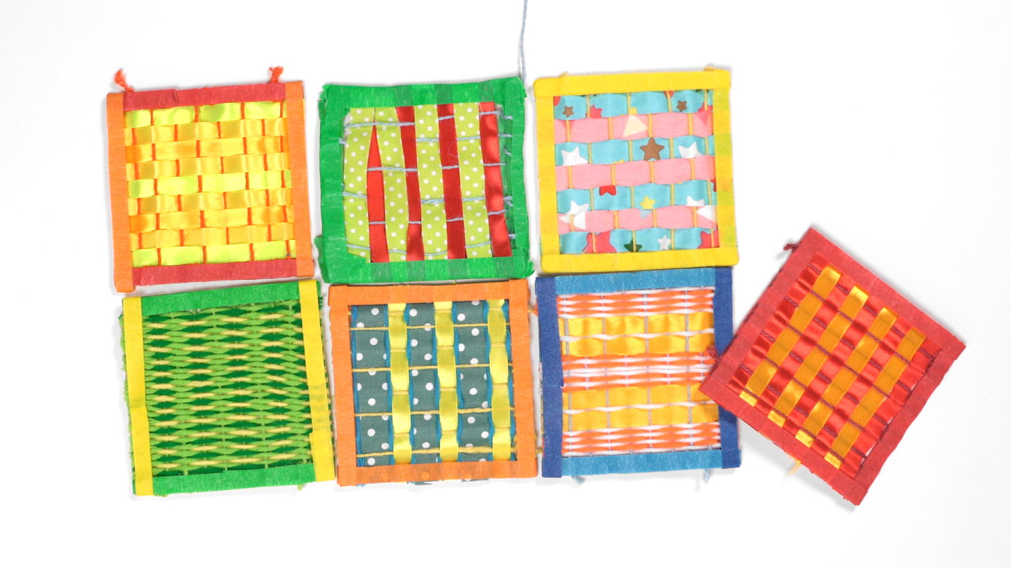 Seven small looms made of popsicle sticks are arranged in two rows.
