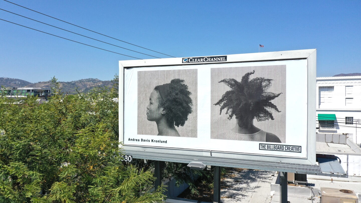 A billboard against a bright blue sky shows two side-by-side photos of a Black woman. The first is a profile shot from the chest up while the second is a photo shot from behind.