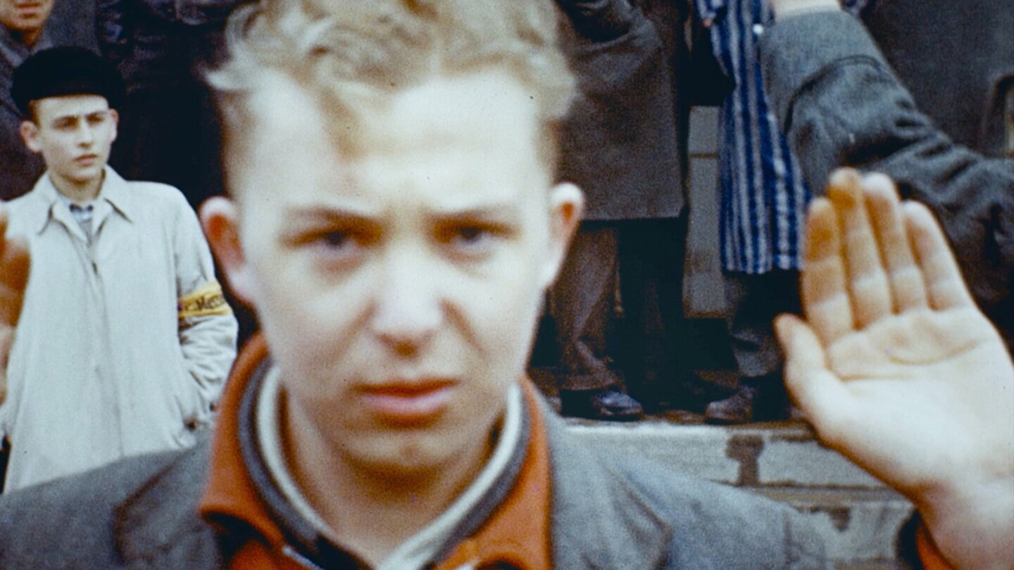 A boy holds up his hands while staring into the camera.