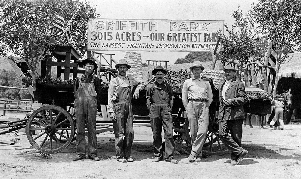"""A group of men stand before a wagon and a painted banner with reads, """"Griffith Park, 3015 acres — Our greatest park. The largest mountain reservation within a city."""" 