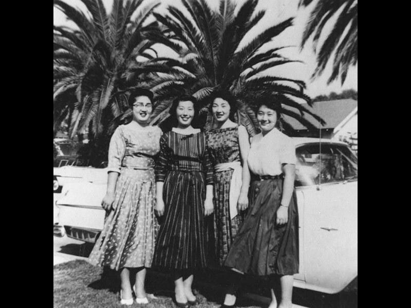 Black and white photo of Setsuko, Taeko, Kou and Keiko Hasegawa posing together under palm trees, 1954