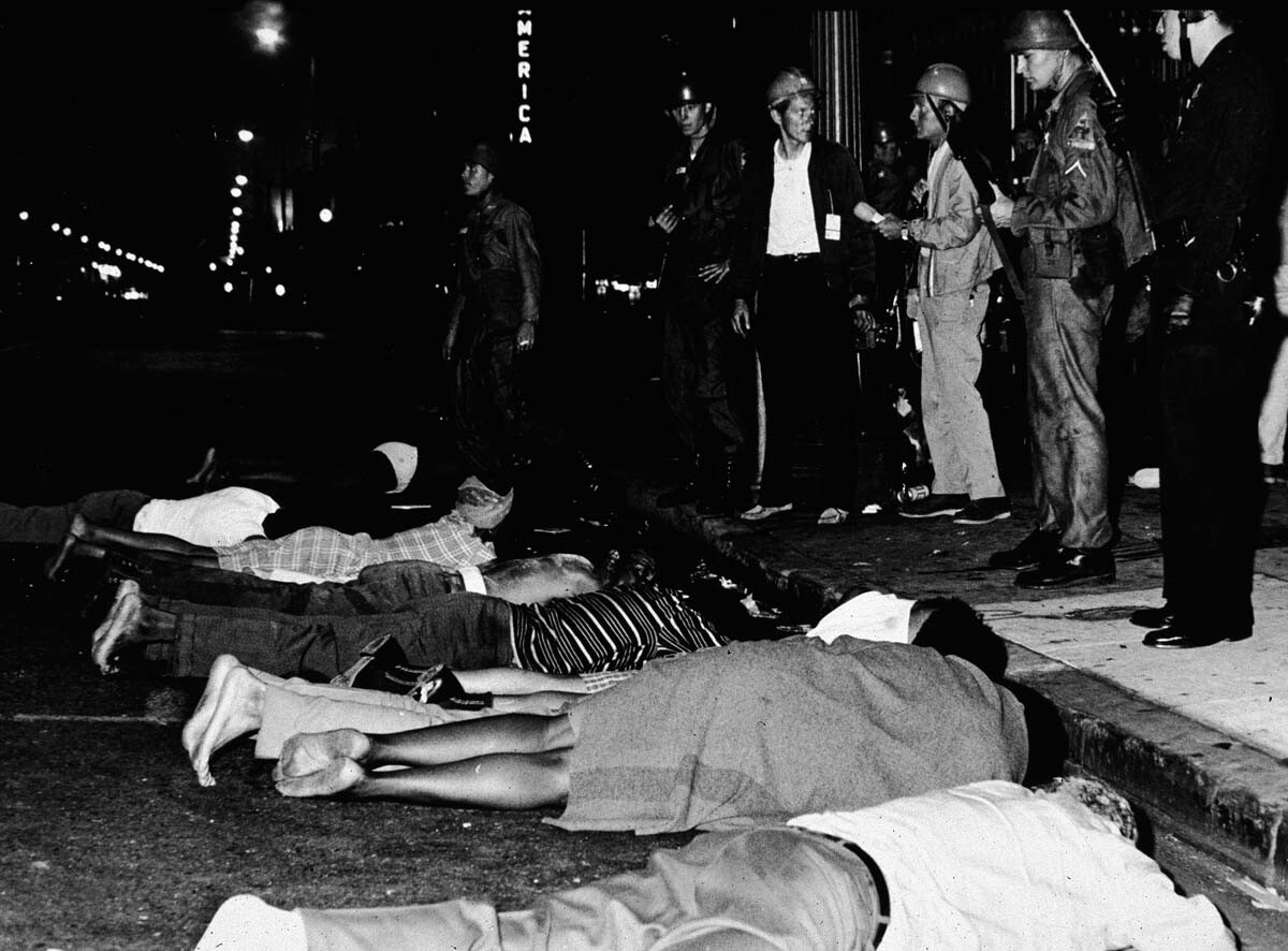 Armed police stand by as rioters lay face down in the street during the Watts race riots, Los Angeles, California, August 1965 | Hulton Archive/Getty Images