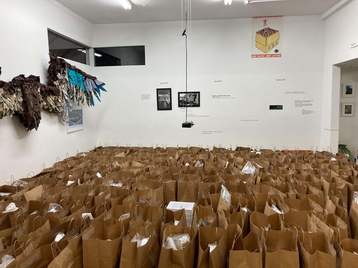 The art supply kits going to high schoolers, packaged in brown paper bags, fill the space at Crenshaw Dairy Mart   Jake Freilich, Ducle Soledad Ibarra and Ana Briz prepare the art supply kits for high schoolers   Courtesy of Crenshaw Dairy Mart