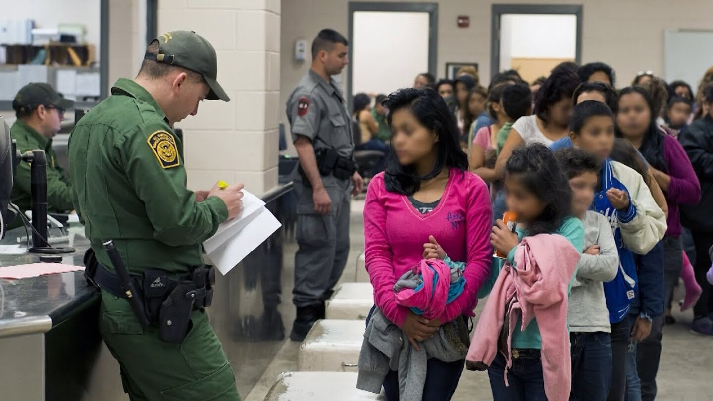A woman and a young girl stand at the front of a line of people waiting to be processed by a U.S. Customs and Border Protection agent. | Democracy Now