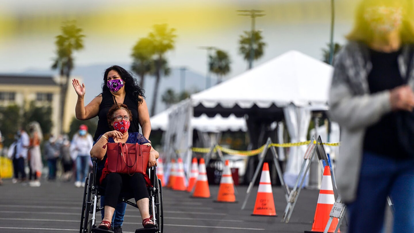 People exit the COVID-19 vaccine super site set up at the north of the Toy Story Parking Lot at the Disneyland Resort in Anaheim, California, on Jan. 13, 2021.