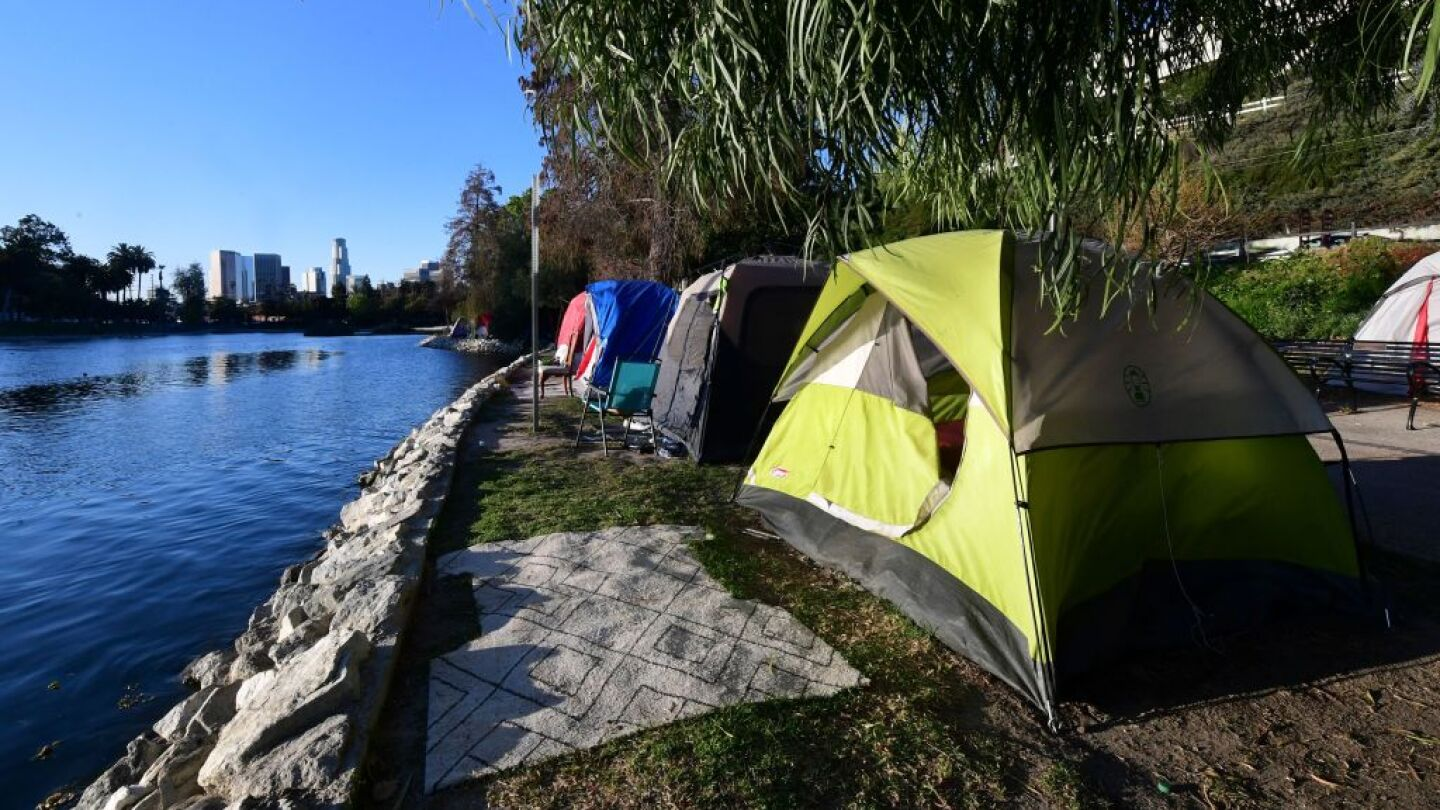 Three camping tents are lined up next to each other in front of a body of water with the Los Angeles skyline in the background.