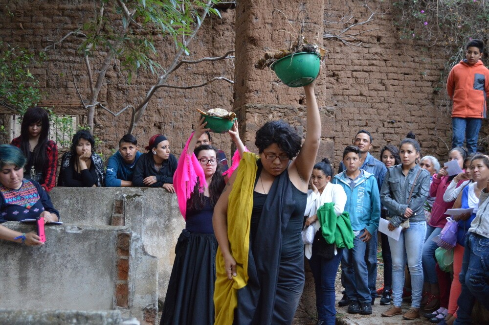 Women in black dress hold up ceramic vessels as people watch in the crowd.