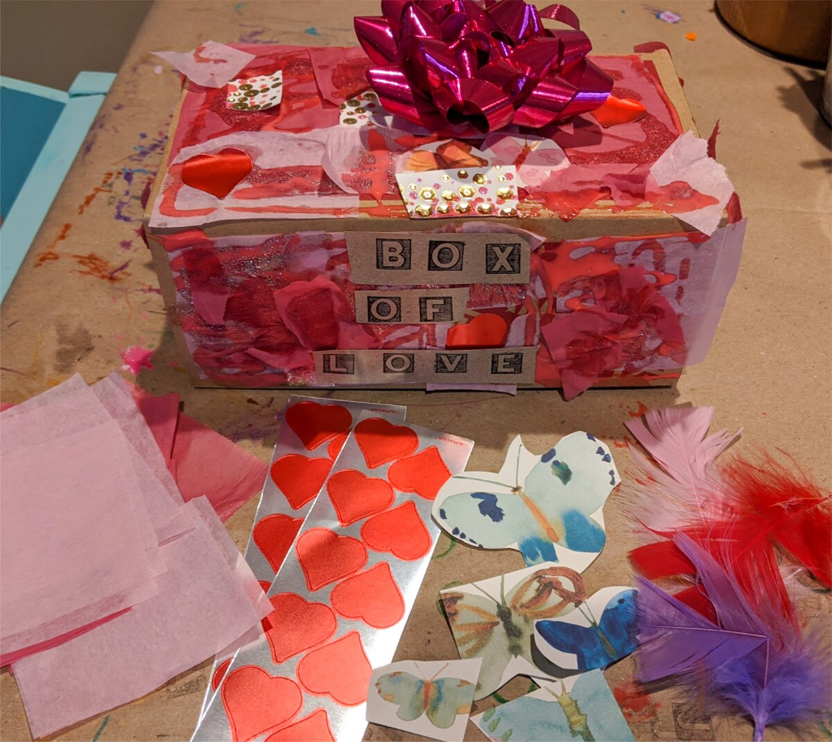 "a highly decorated box with a bow and the words ""box of love"" on it"