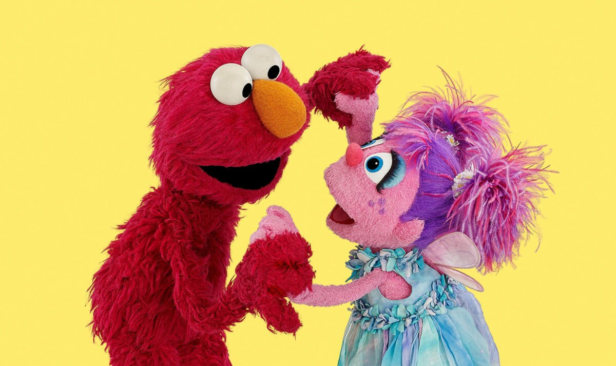 A red and pink Muppet play together