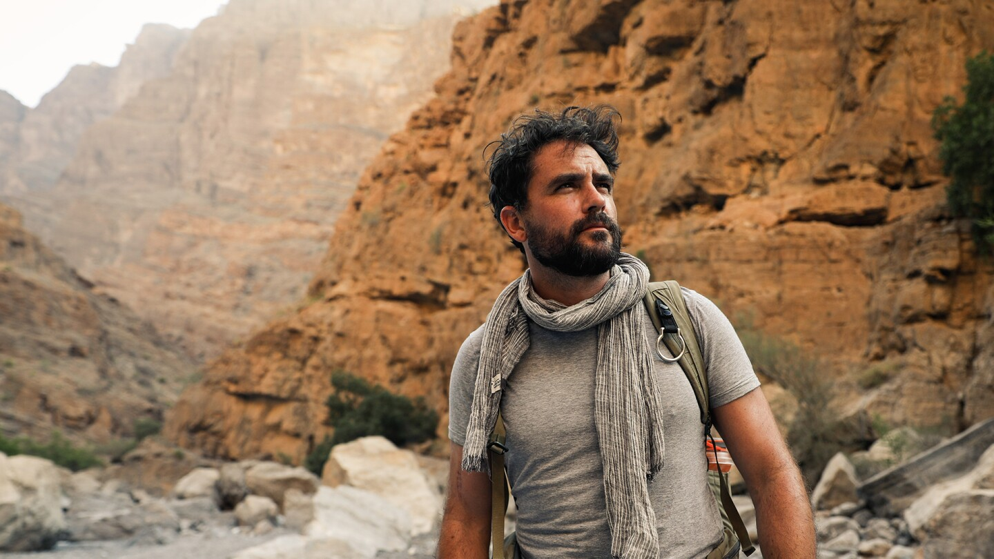"""Levison Wood stands at the base of a rocky mountain. 