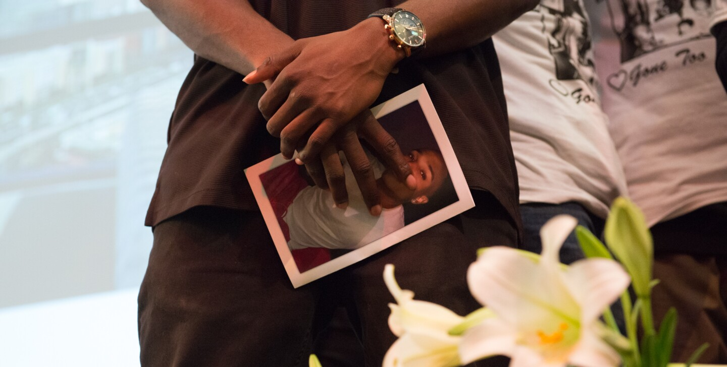 "A friend of Josiah Lawson at his memorial, holding a photo of David Josiah Lawson in his hands. | Still from ""Who Killed Josiah?"" 