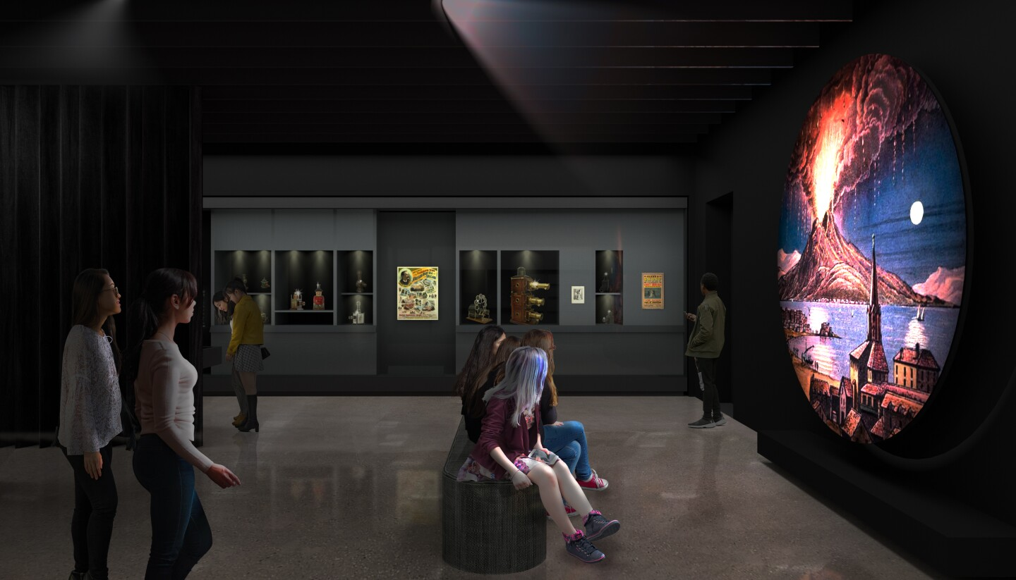"""A rendering of """"The Path to Cinema: Highlights from the Richard Balzer Collection,"""" an exhibition at the Academy Museum of Motion Pictures set to open Sept. 30. The image depicts museum-goers in a dark room viewing a circular screen displaying an image of an erupting volcano."""