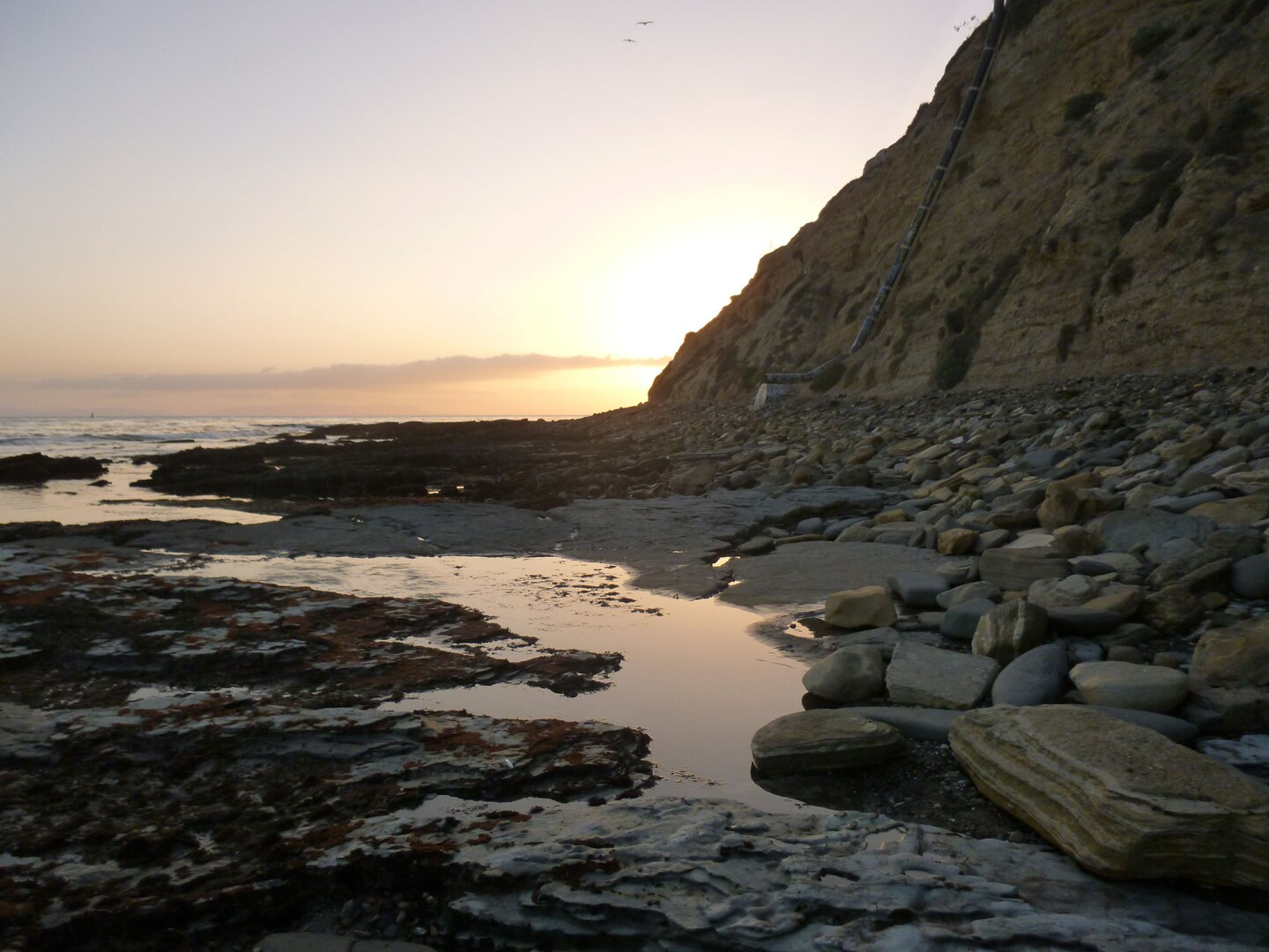 A sunset shines a warm glow on an almost dry shore of Cabrillo Beach in San Pedro.