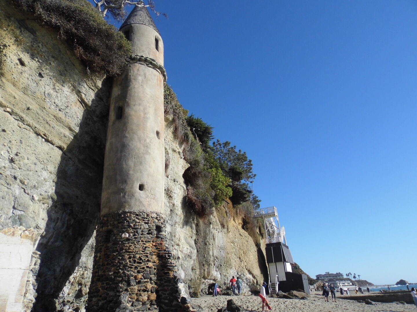 Locals walk along the coast of Victoria Beach as the medieval-looking tower stands over them.