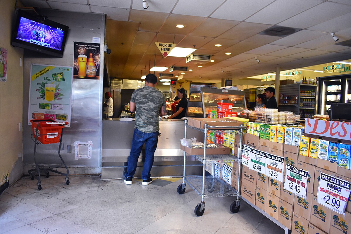 A customer picking up food pre-ordered from the turo-turo section, near the entrance way. | Jacqueline Lee