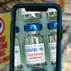 A smartphone screen showing a vial of COVID-19 vaccine.