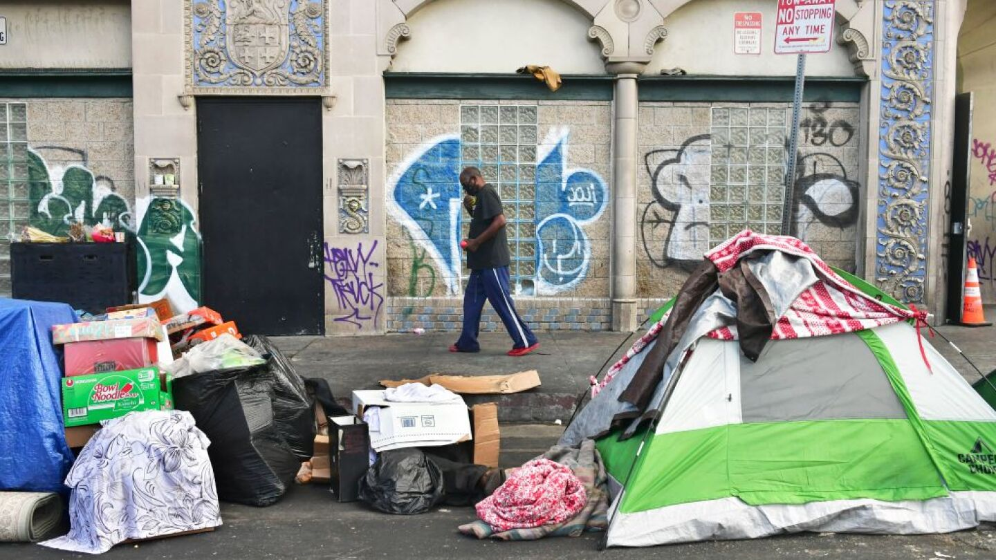 A man walks past tents housing the homeless on the streets in the Skid Row community of Los Angeles, California on April 26, 2021.