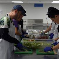 Participants of L.A. Kitchen's food culinary training program chop vegetables. Still from video by Chase Alexander