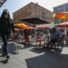 A woman with a dog walks by Grand Central Market on Tuesday, March 30, 2021 in Los Angeles , CA
