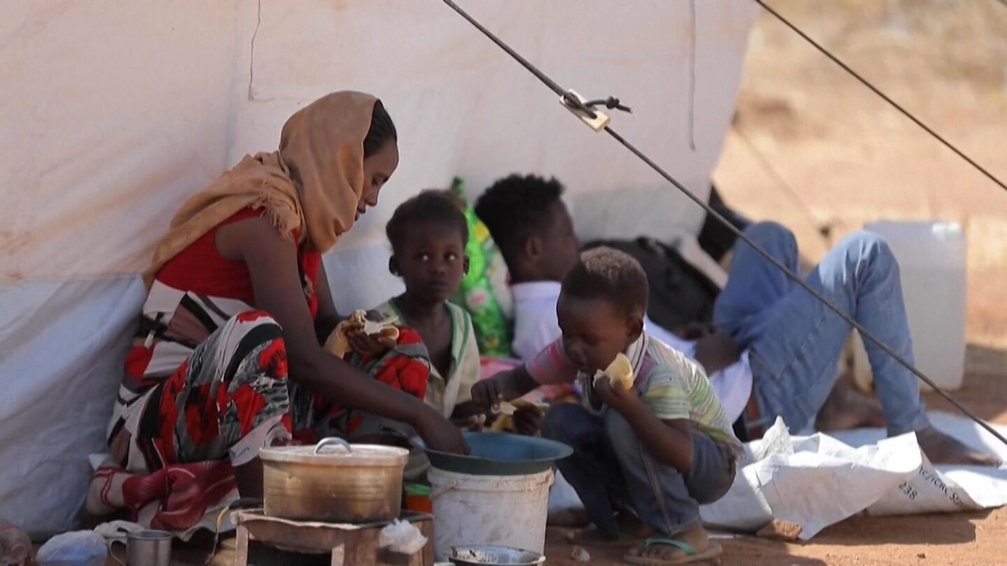 A small family in Ethiopia's Tigray region eat bread against a tent.