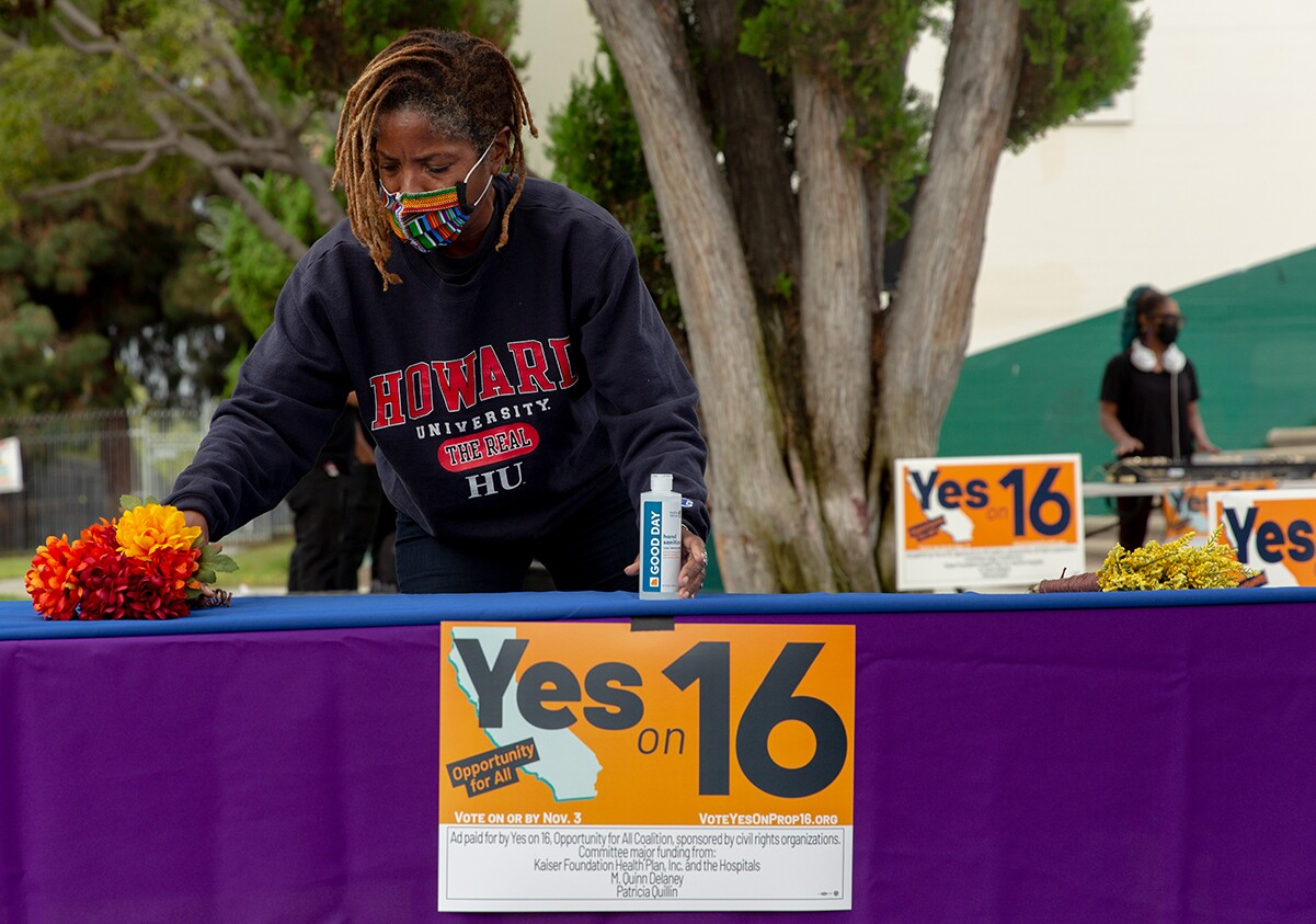 Apryl Sims sets up in support of a Proposition 16 rally at Dorsey High School in Los Angeles | Allison Zaucha for The Washington Post via Getty Images