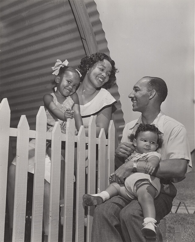 Mother and father holding children at Roger Young Village | Housing Authority of the City of Los Angeles