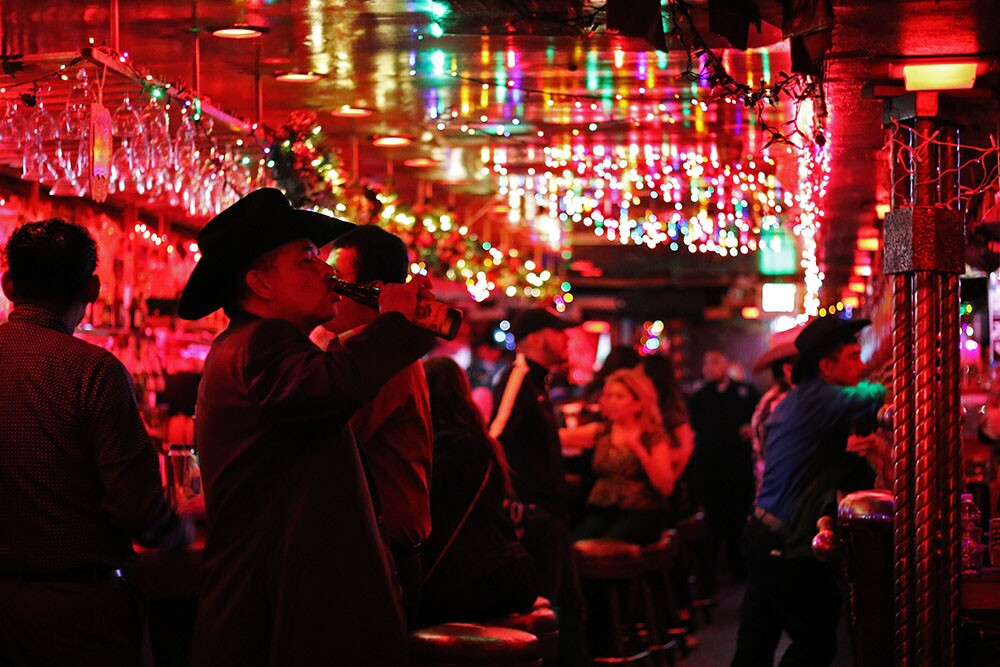Scene from inside La Cita with men in hats and festive lighting.   Samanta Helou