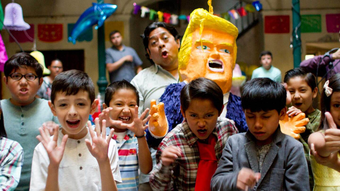 Group of children celebrating a birthday around a Trump piñata. | La Madre Buena