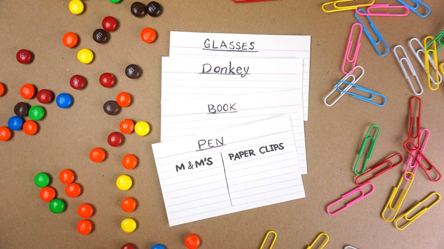 Several index cards (one for each item) are used to write down how much each thing measures in clips and candies.