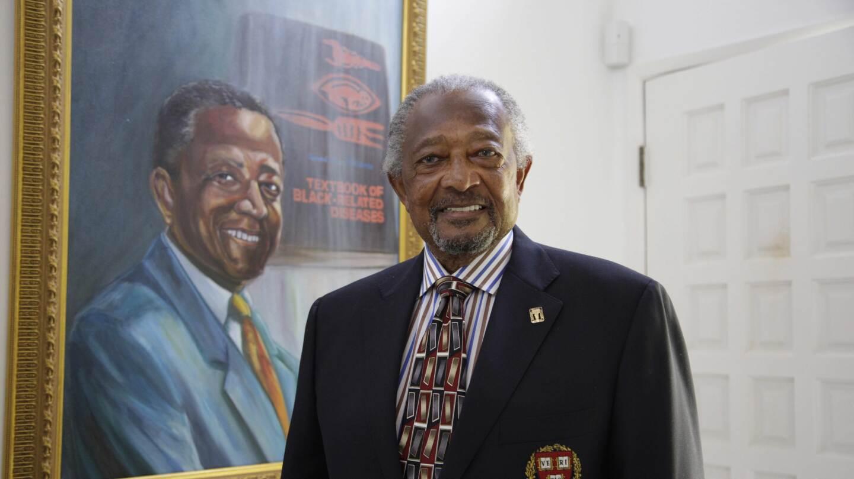 Dr. Richard Allen Williams stands beside a framed poster of his novel.